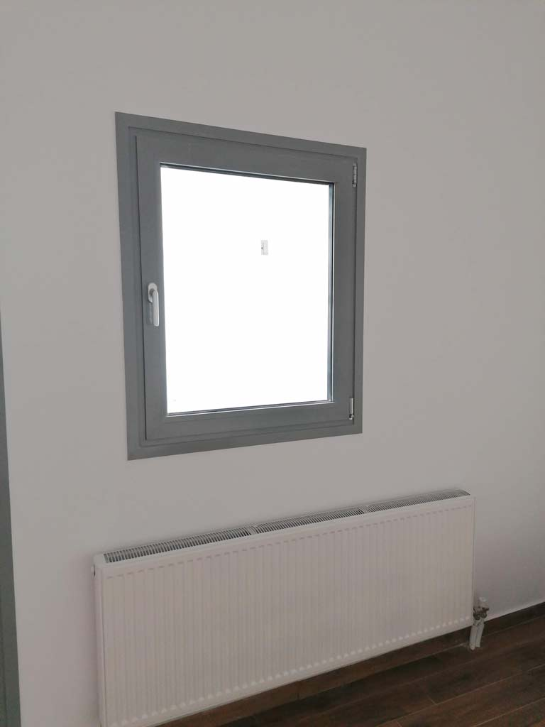 καλοριφέρ κάτω από παράθυρο σαλονιού